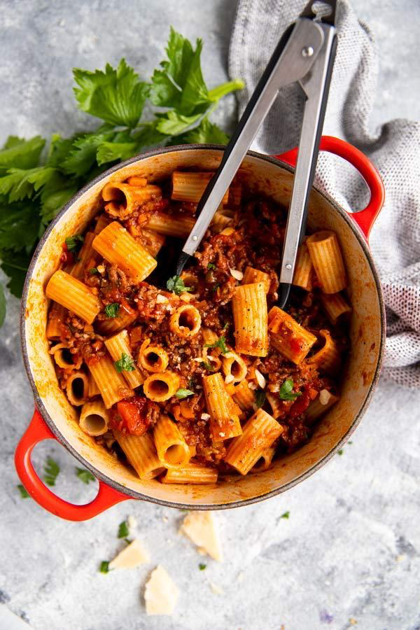 roter gusseiserner Topf, gefüllt mit Rigatoni in Bolognese Sauce