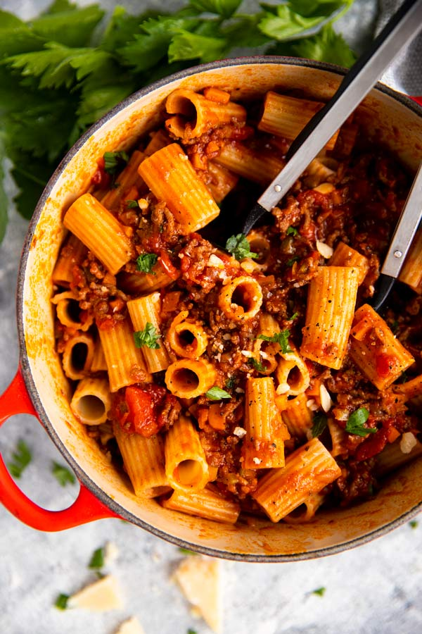 roter gusseiserner topf mit rigatoni bolognese