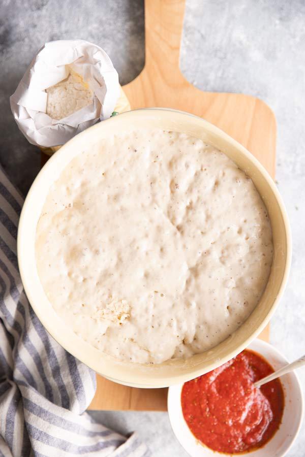 Schüssel mit selbstgerechtem Pizzateig, daneben eine Schale mit Tomatensauce und eine Packung Mehl