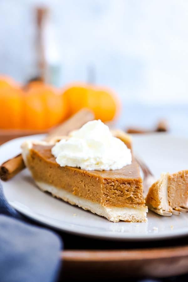 Pumpkin Pie auf einem Teller mit ener Gabel und Kürbissen im Hintergrund