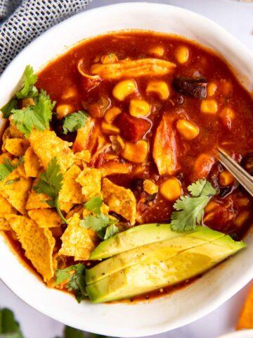 schale mit Mexikanischer Hühnersuppe, Tortilla Chips und Avocado