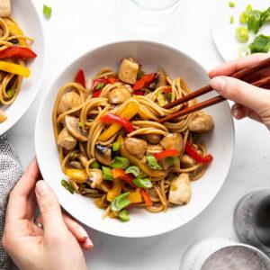weibliche Hände halten Stäbchen in einen Teller mit Asia-Nudeln