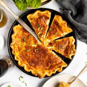 geschnittene Quiche Lorraine von oben auf einem Tisch mit Salat und Tellern