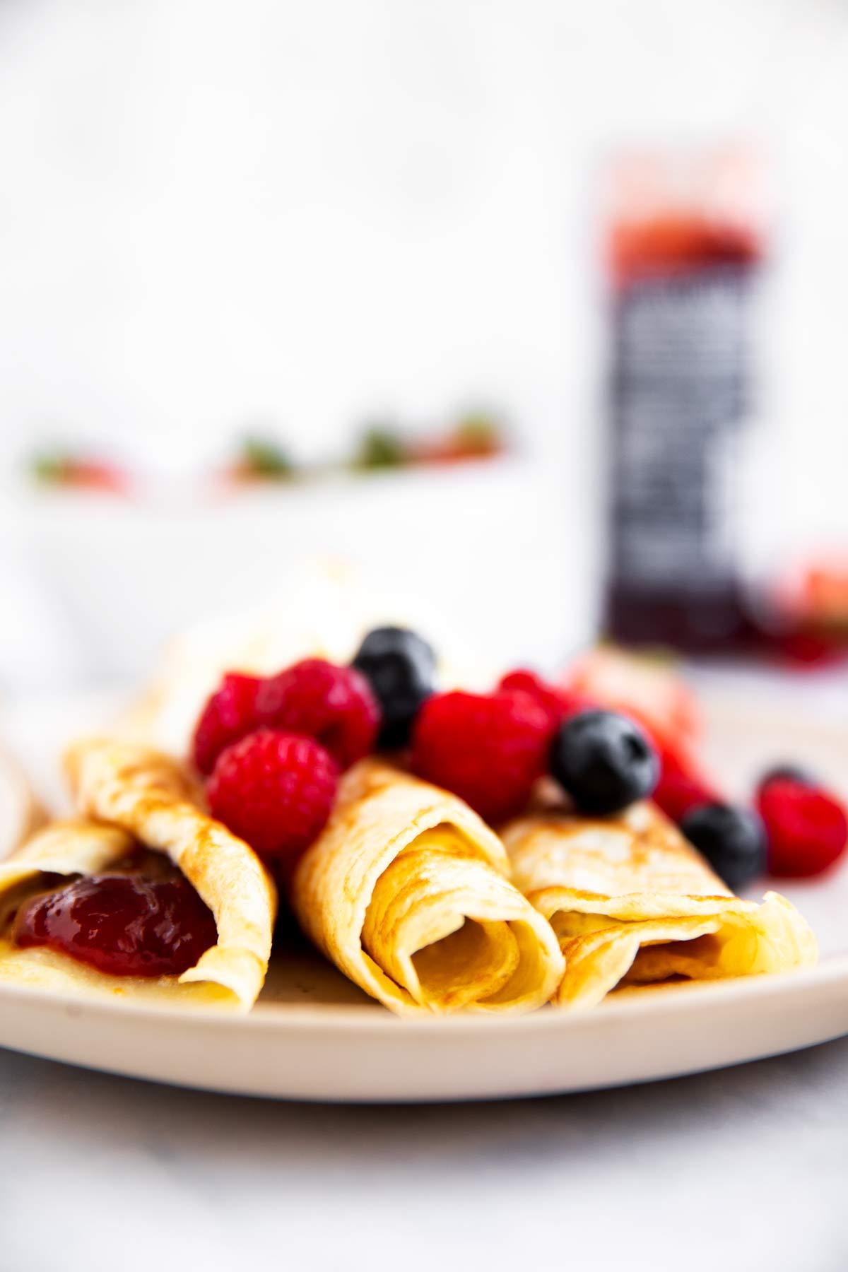 Teller mit Pfannkuchen mit Beeren und Marmelade im Hintergrund