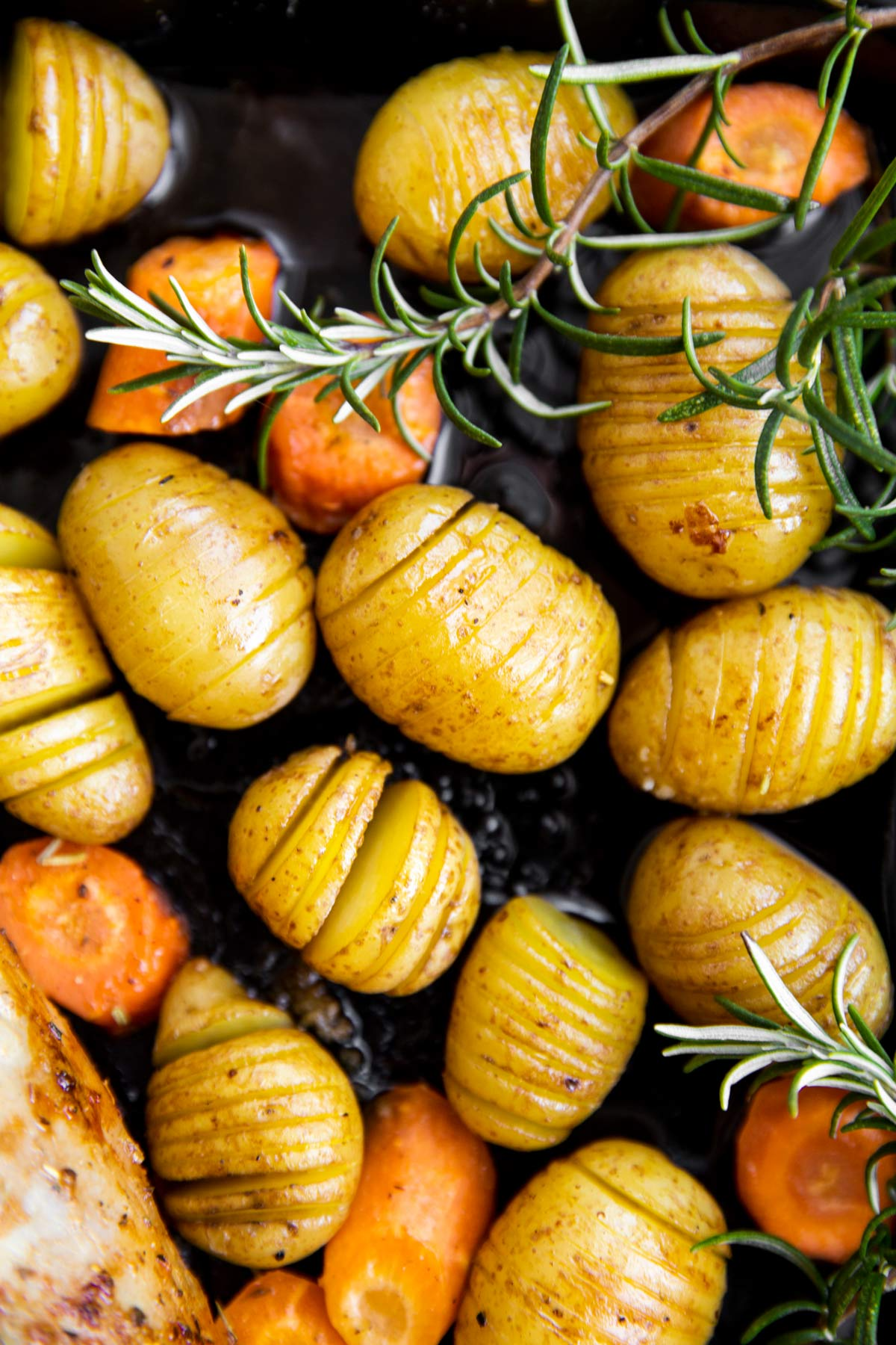 Fächerkartoffeln mit Karotten auf einem Blech