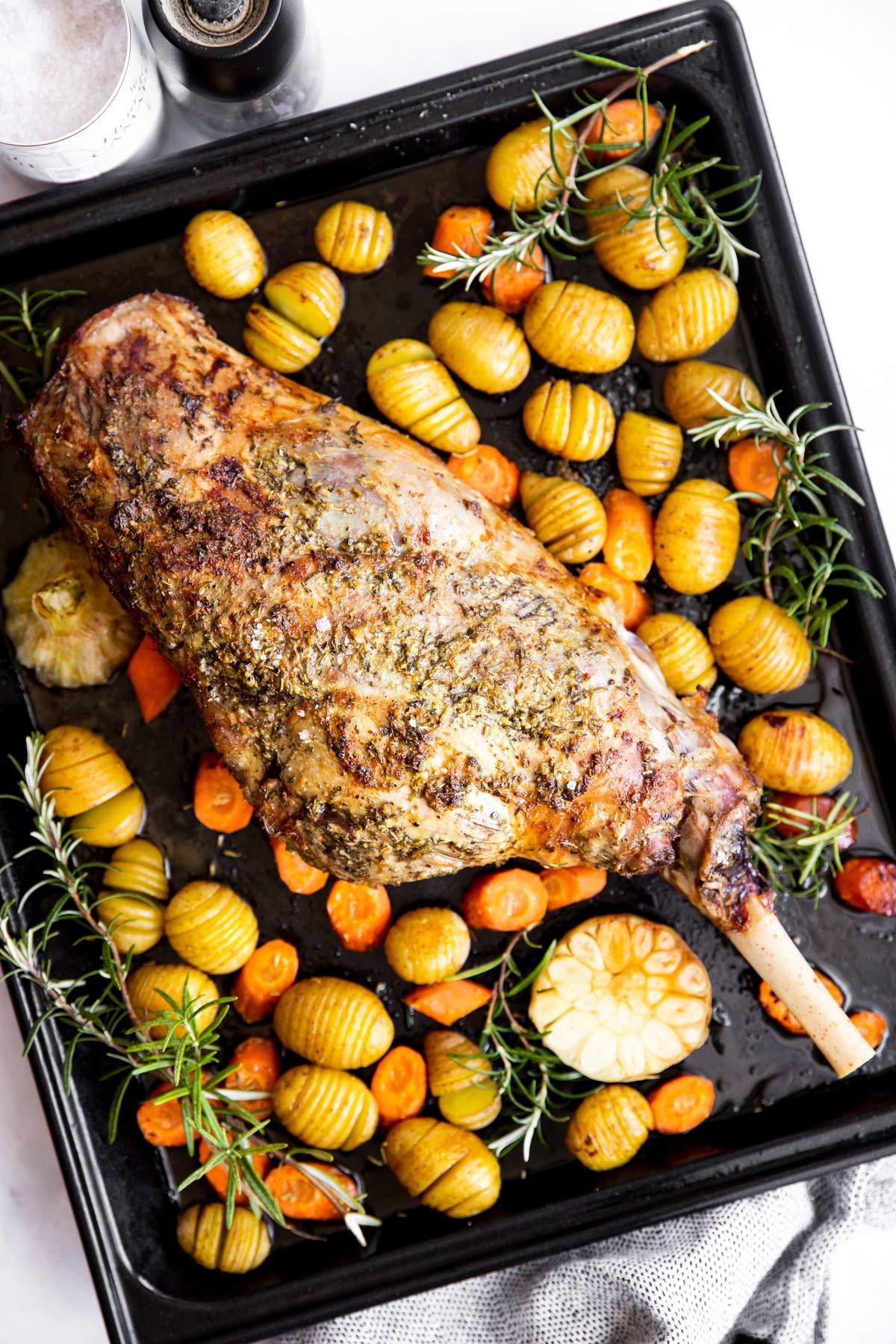 gebackene Lammkeule auf einem Blech mit Kartoffeln und Karotten