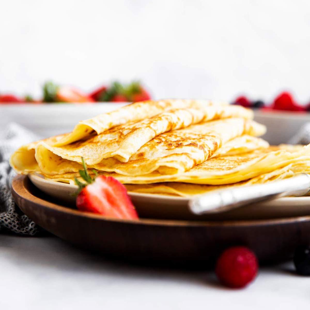 Stapel Pfannkuchen auf einer Platte mit Beeren