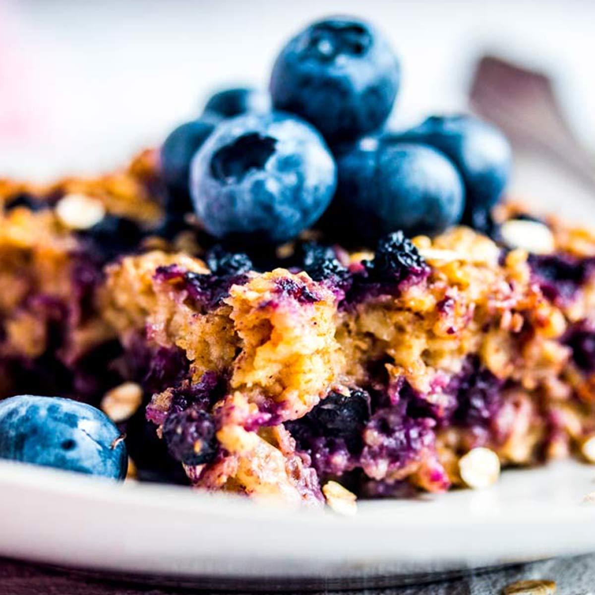 Stück von Baked Oatmeal auf Teller mit frischen Blaubeeren