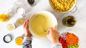 Weibliche Hände rühren Hörnlisalat Sauce